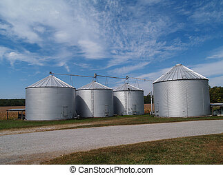 Four farm silos beside a country rock road in front of ripening soybean field with plenty of copy space.