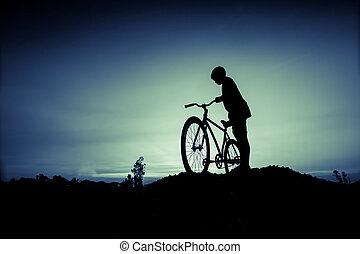 silueta, de, crianças, e, bicicleta, em, pôr do sol