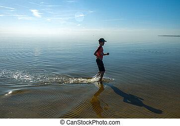 silueta, de, feliz, adolescente, chico que corre, en orilla
