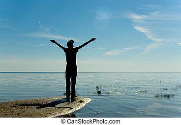 silueta, de, feliz, adolescente, niño, en orilla