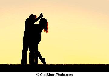 silueta, de, feliz, el bailar joven de los pares, en, ocaso