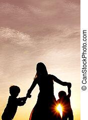silueta, de, feliz, madre, y, poco, niños, bailando, exterior, en, ocaso