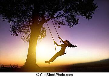 silueta, de, feliz, mulher jovem, ligado, um, balanço, com, pôr do sol, fundo
