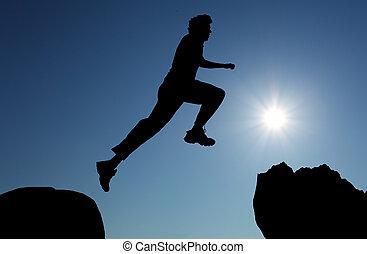 silueta, de, hiking, homem saltando, sobre, a, montanhas, em, pôr do sol