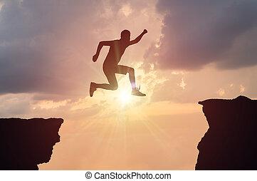 silueta, de, homem saltando, sobre, um, lacuna, em, sunset.
