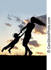 silueta, de, madre, girar, y, bailando, con el niño, en, ocaso