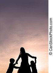 silueta, de, madre y niños, bailando, en, ocaso