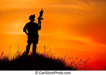 silueta, de, militar, soldado, ou, oficial, com, armas, em, sunset.