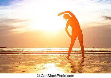 silueta, de, mujer joven, ejercicio, en la playa, en, sunset.