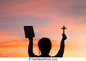 silueta, de, mujer joven, manos, tenencia, biblia santa, y, levantamiento, de, cristiano, cruz, con, luz, ocaso, fondo.