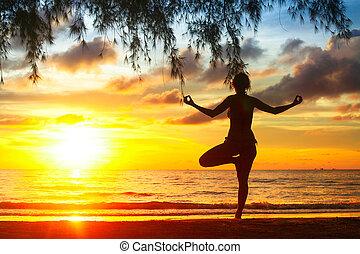 silueta, de, mujer joven, practicar, yoga, en la playa, en, sunset.