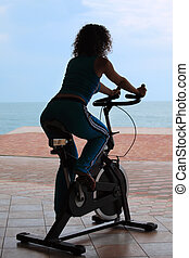 silueta, de, niña, en, bicicleta, entrenamiento, aparato, al aire libre