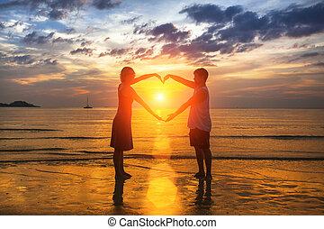 silueta, de, par amoroso, durante, um, espantoso, pôr do sol, segurar passa, em, coração, forma.