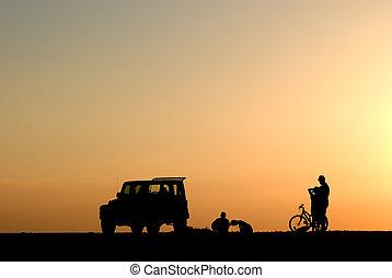 silueta, de, pessoas, carros, e, bicicleta, em, pôr do sol