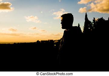 silueta, de, só, homem jovem, plataformas, ligado, a, montanha, e, olha, em, a, distância