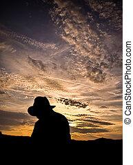 silueta, de, um, boiadeiro, com, chapéu, em, pôr do sol