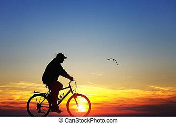 silueta, de, um, homem, ligado, bicicleta, em, pôr do sol