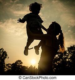 silueta, de, um, mãe filho, quem, jogo, ao ar livre, em, pôr do sol, fundo