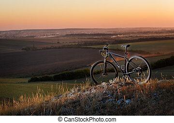 silueta, de, un, bicicleta, en, el, colinas, en, sunset.