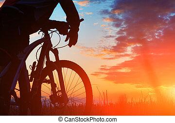 silueta, de, un, biker, y, bicicleta, en, ocaso, fondo.