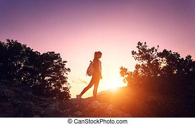 silueta, de, un, feliz, mujer joven, en, montañas, en, ocaso