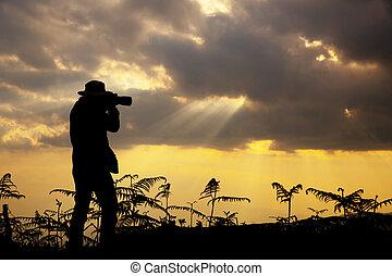 silueta, de, un, fotógrafo, quién, retoños, un, ocaso, en las montañas