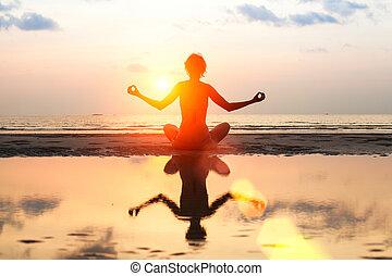 silueta, de, un, hermoso, yoga, mujer, en la playa, en, ocaso