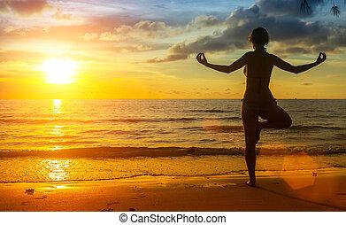 silueta, de, un, mujer joven, yoga, ejercicio, en, el, océano, playa, en, ocaso, time.