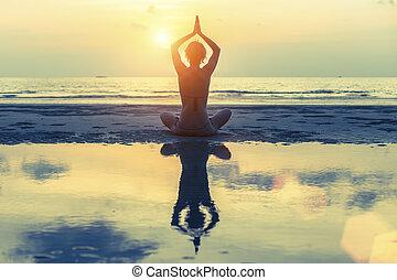 silueta, de, un, niña joven, (with, reflexión, en, el, water), practicar, yoga, en la playa, durante, sunset.