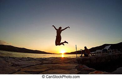 silueta, de, un, niña, saltar, en, ocaso, en la playa