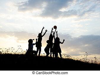 silueta, grupo, de, feliz, jogar crianças, ligado, prado, pôr do sol, verão