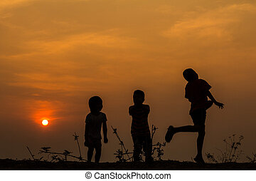 silueta, grupo, de, feliz, niños jugar, en, pradera, ocaso, s