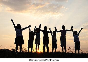 silueta, grupo, de, feliz, niños jugar, en, pradera, ocaso,...