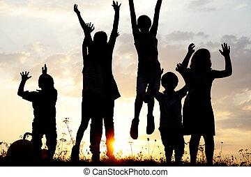 silueta, grupo, de, feliz, niños jugar, en, pradera, ocaso, verano