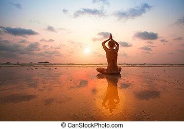 silueta, mujer joven, practicar, yoga, en, el, mar, playa, en, sunset.