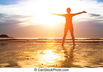 silueta, mulher jovem, exercício, praia, em, sunset.