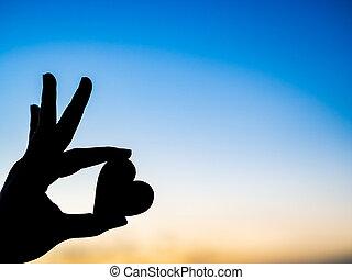 silueta, tenencia de la mano, hermoso, corazón, durante, ocaso, fondo., feliz, amor, día de valentín, idea, señal, símbolo, concept.