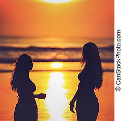 siluetas, de, dos niñas, contra, puesta sol roja, en la playa