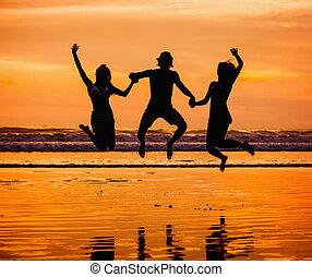siluetas, de, feliz, joven, amigos, saltar, en la playa, contra, puesta sol roja