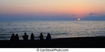 siluetas, de, joven, grupo de las personas, en, el, ocaso, cerca, el, mar