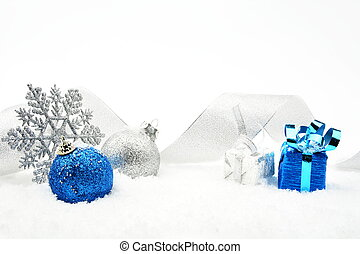 Silver and blue christmas glittering baubles with ribbon on snow