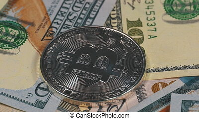Silver Bitcoin Coin, BTC and Bills of Dollars are Rotating. Crypto Currency Close-up. Dollar banknotes of various denominations on which lies the cryptocurrency.