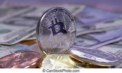 Silver Bitcoin Coin, BTC and Bills of Dollars are Rotating. Different Crypto Currency Close-up. Macro. Dollar banknotes of various denominations on which lies the cryptocurrency.