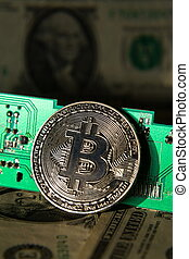 Silver bitcoin coin with dollars and computer motherboard, cryptocurrency mining concept