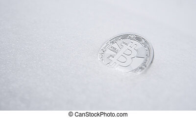 Silver bitcoin. Cryptocurrency on snow, in the background. The concept of freelancing, the stock exchange. Gold bitcoin on cold winter snow background. Frozen bitcoin. Frozen account. Trading.