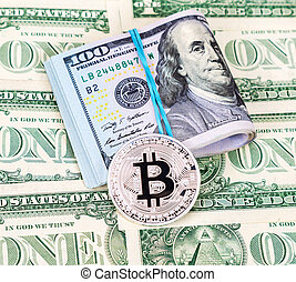 Silver bitcoin of cryptocurrency and folded american dollars over dollar banknotes, close up