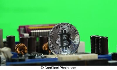 Silver bitcoin on the computer motherboard background...