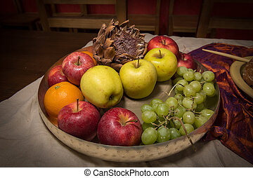 Silver bowl with various fruits standing on a table