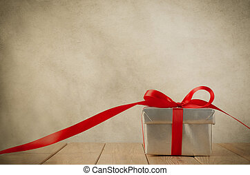 A silver gift box with red ribbon on wood plank table. Ribbon trails off to the side and faces front. Old grungy parchment effect gives a vintage feel. Copy space above and on ribbon.