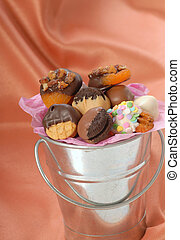 Silver bucket containing a variety of delicious chocolate covered candies and nuts